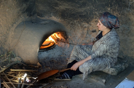 Woman cooking traditional flatbread in a wood fired oven
